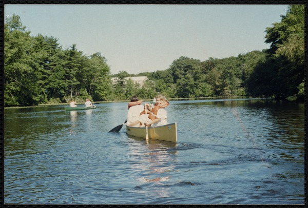 Children navigate canoes on a lake.