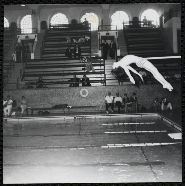 A boy performs a dive at a Boys' Club swimming championship